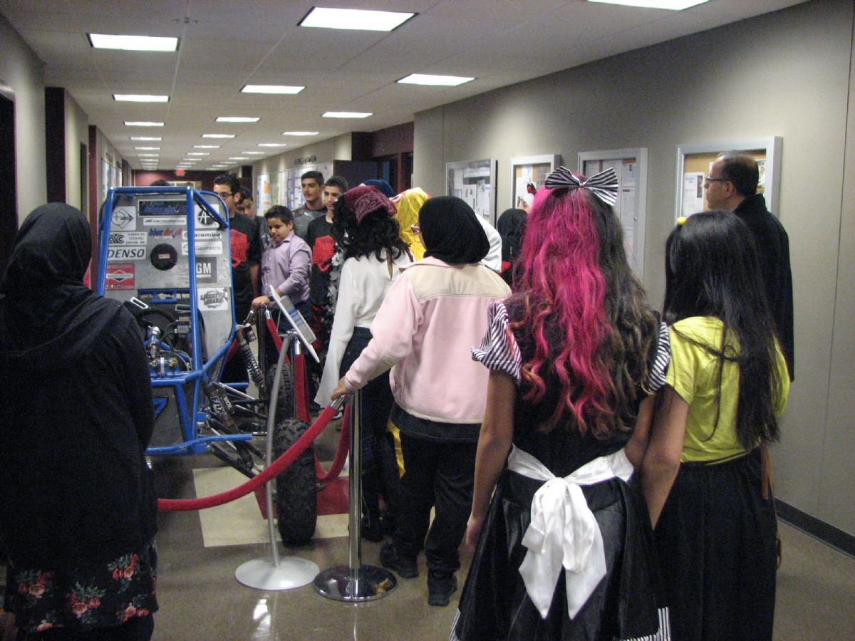 Lowrey students looking at a competition vehicle in the Engineering building hallway