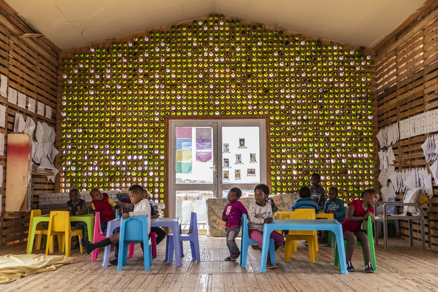 1,500 discarded wine bottles to build this wall at a preschool