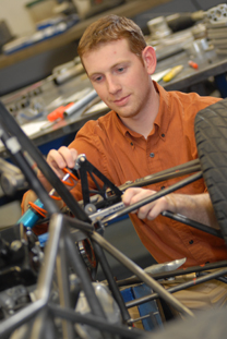 Mechanical engineering student works on car